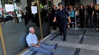 Un financier australien tend la main au retraité grec qui pleure 5